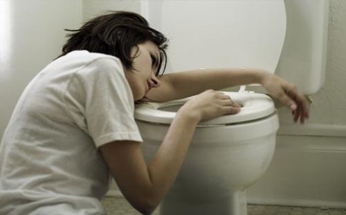 mulher debruçada em cima da patente após vomitar
