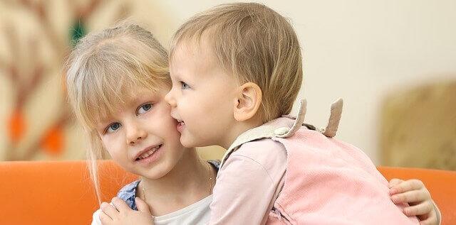 duas crianças dando um beijo no rosto