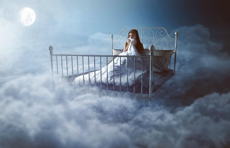 menina deitada em uma cama nas nuvens, sonhando acordada