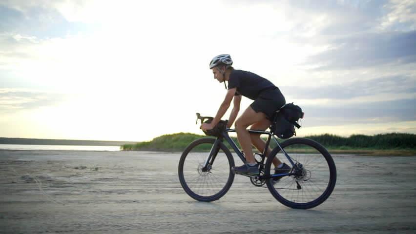 homem andando de bicicleta na praia