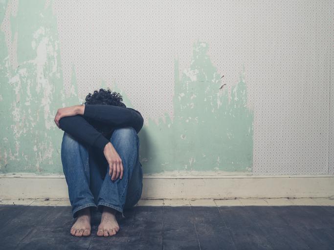 pessoa triste sentada no chão