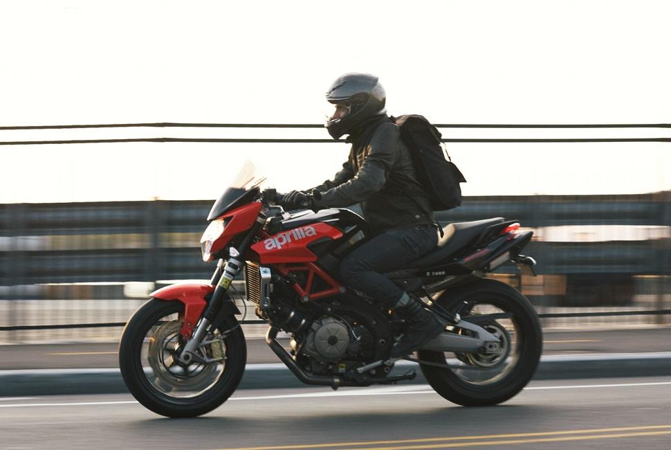 homem pilotando uma moto sozinho ao entardecer