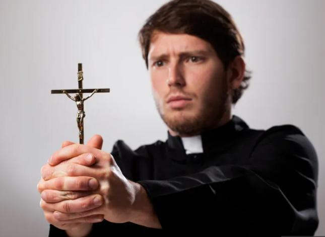 padre segurando uma cruz para fazer um exorcismo