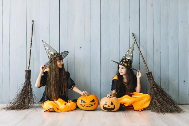 meninas fantasiadas no halloween com vassouras de bruxas