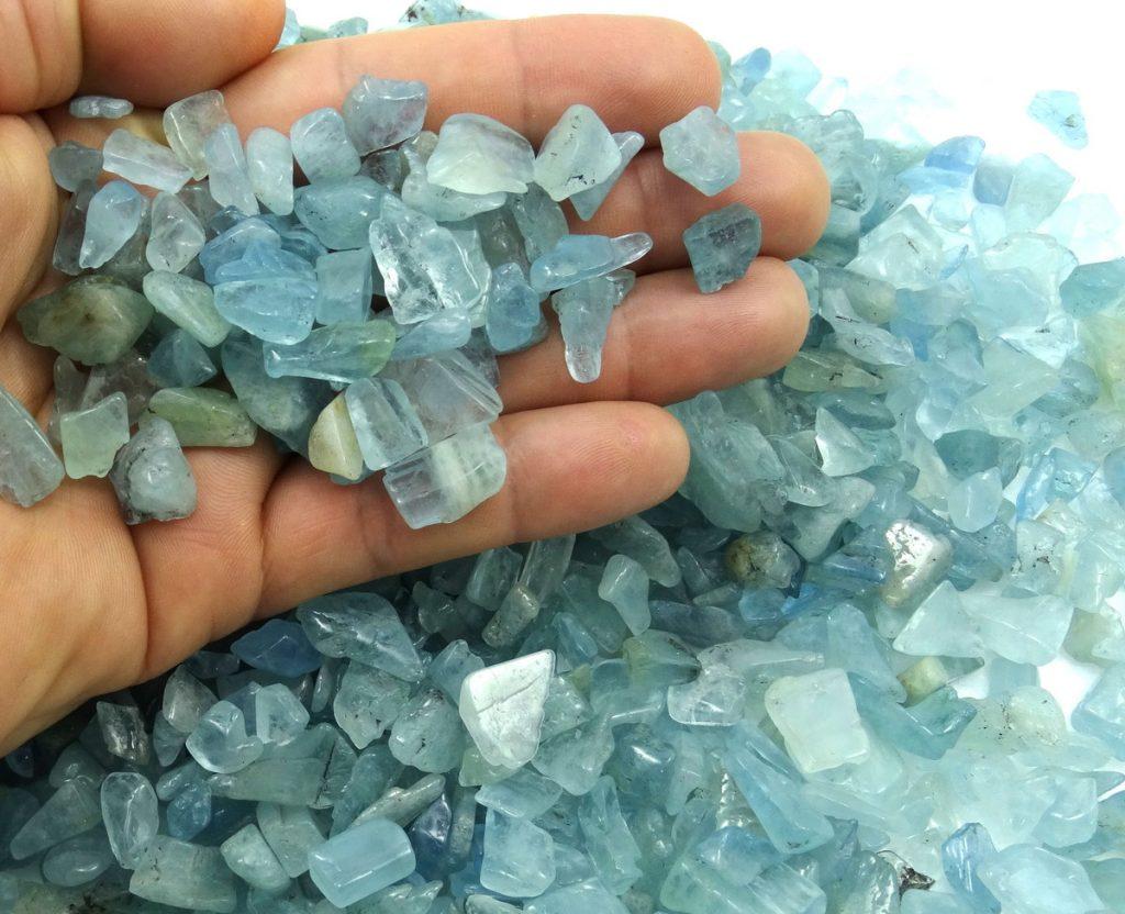 uma mão segurando pequenas pedras agua marinha brutas
