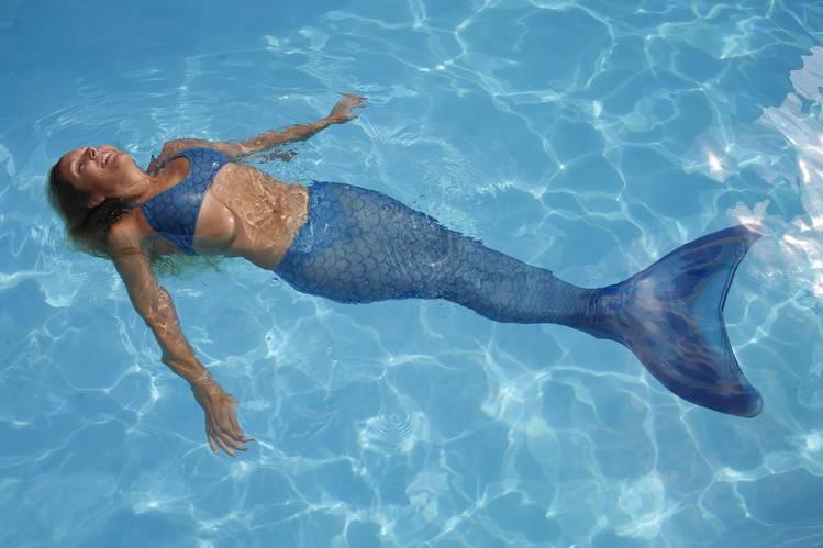 sereia com calda azul flutuando sobre a piscina