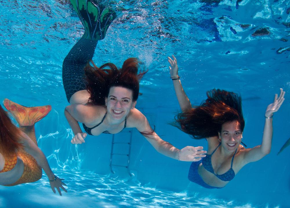 três sereias nadando livremente na piscina