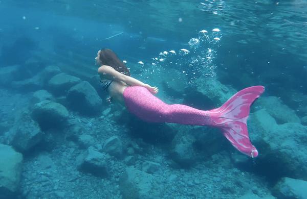sereia nadando livremente no mar com uma calda rosa