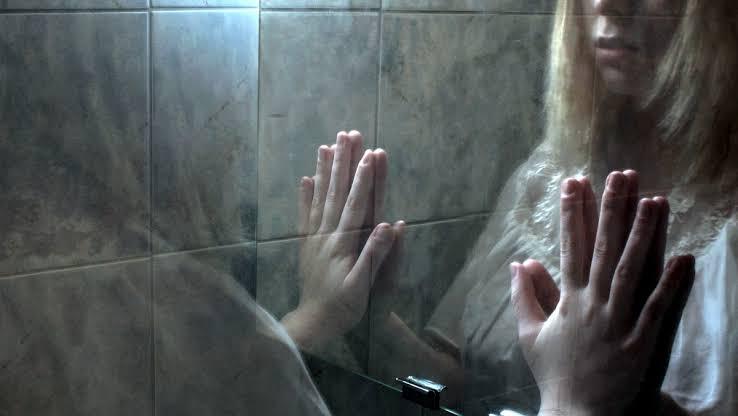 loira do banheiro se olhando no espelho
