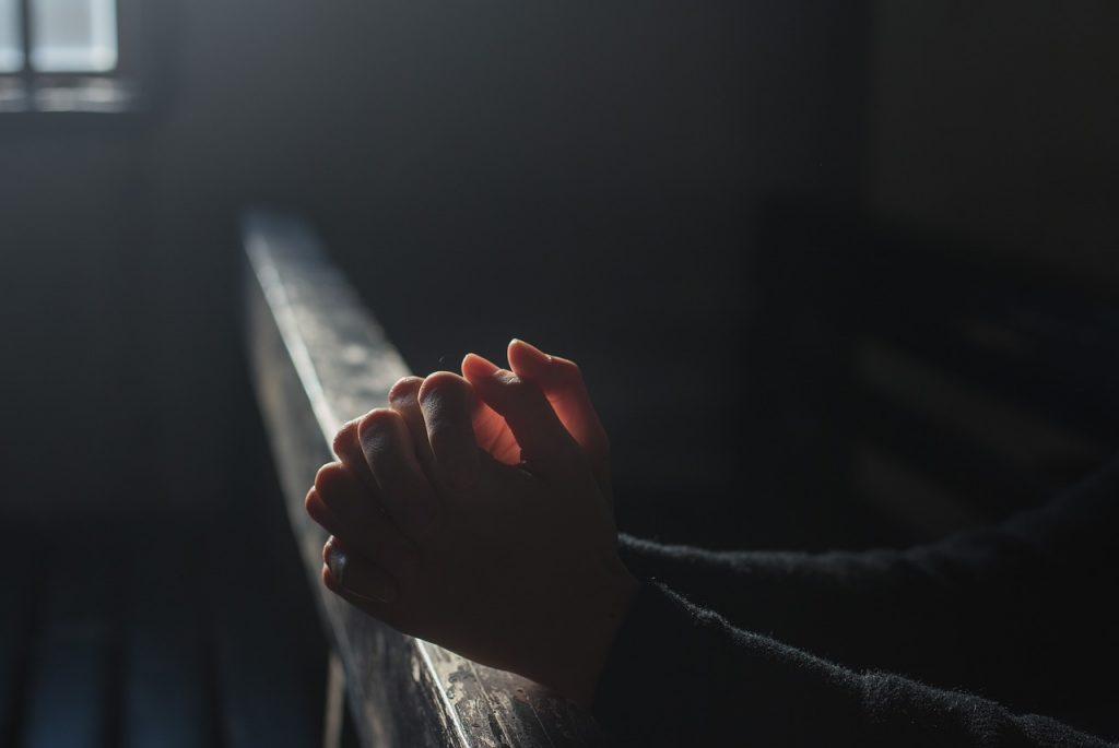 pessoa de maos juntas orando na igreja