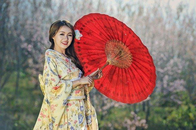 mulher chinesa segurando um guarda-chuva vermelho