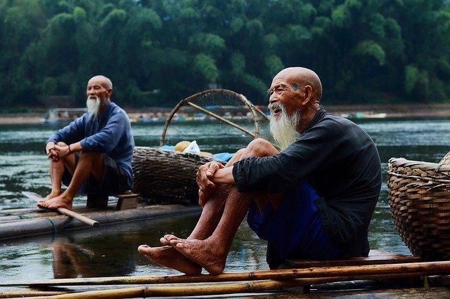 dois homens chineses em barcos no mar