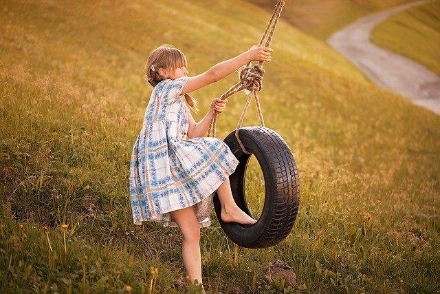 garota subindo em um balanço de pneu