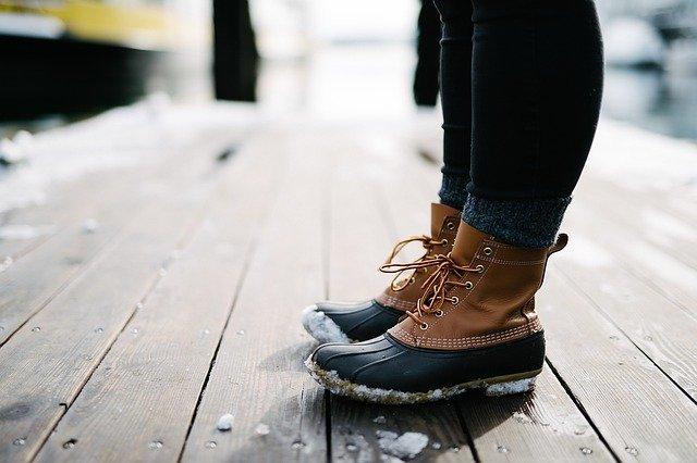 botas de neve em um deck de madeira