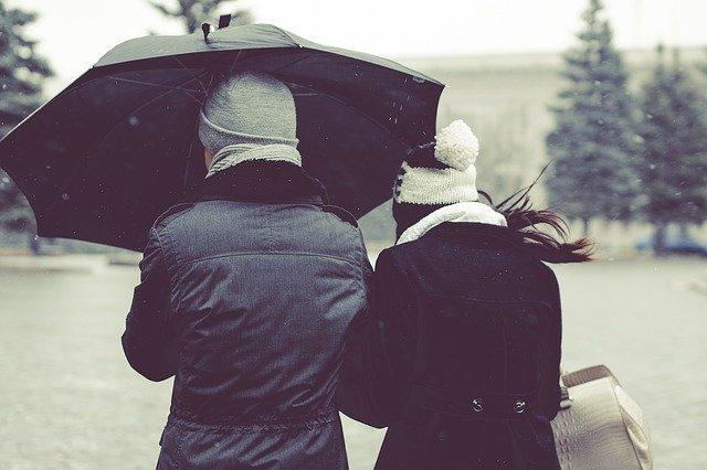 casal de costas segurando um guarda-chuva