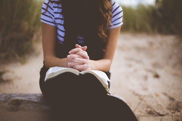 mulher orando com a bíblia no colo