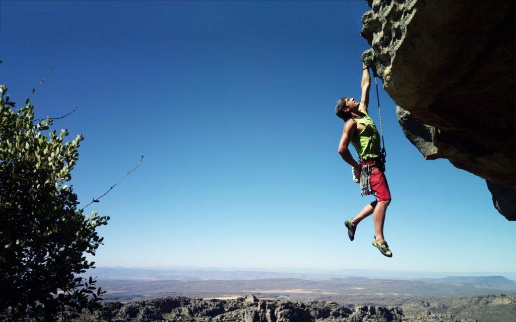 homem se segurando em uma rocha para não cair no penhasco