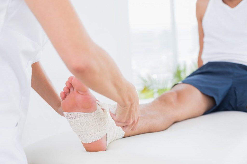 enfermeira cuidando da ferida do pé de uma pessoa
