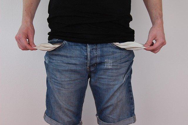 homem com os bolsos vazios de dinheiro