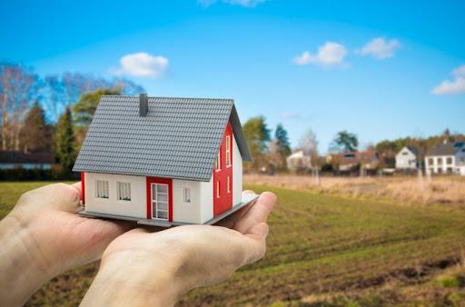 pessoa segurando uma miniatura de uma casa