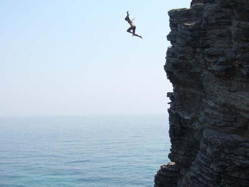homem pulando de um penhasco alto